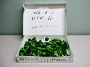 doughnut box filled with broccolli saying 'We ate them all - have some broccolli'