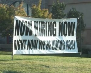 Sign saying - now hiring now right now we're hiring now