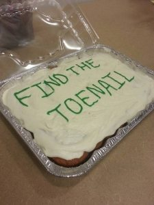 photo of cake with icing saying 'Find the toenail'