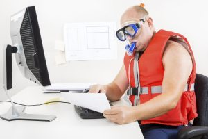 Funny office worker in life vest and scuba diver gear at the office. Combines vacation and work.
