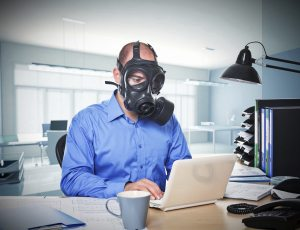 man in office with gas mask
