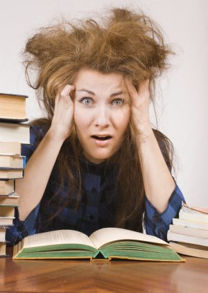 Girl studying with books shows panic expression