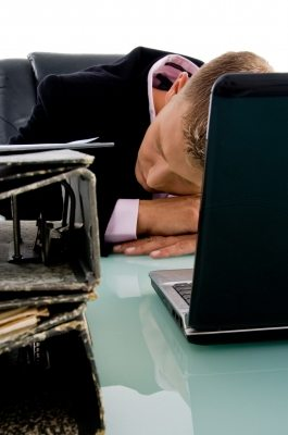 a businessman sleeping at the laptop