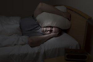 Man in dark with pillow over head