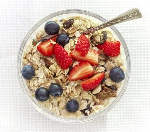 healthy breakfast, bowl of muesli with milk and fresh berries