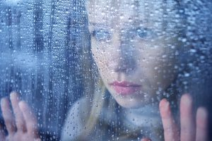 woman looking out of the window sadly - into the rain