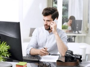 man on phone with computer up