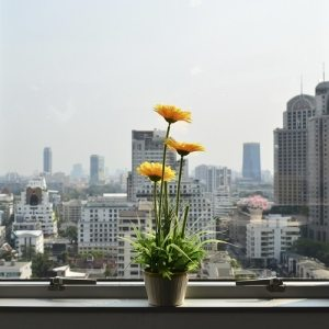 flowers sat on a window sill looking out on a city