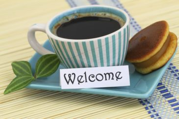 cup of coffee and cake and a note saying welcome