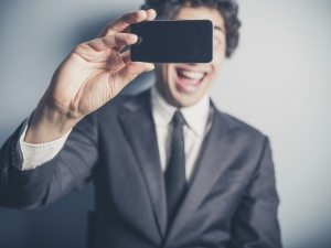 A young busnessman is using his smartphone to video himself