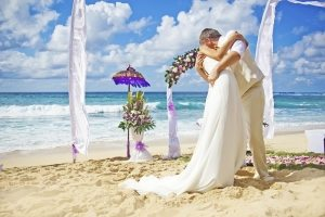bride and groom at a beach wedding kissing