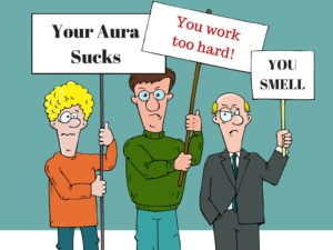 3 men holding up signs saying 'your aura sucks' 'you work too hard' and 'you smell'