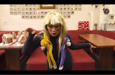 woman in blonde wig with toy moneys tired round her neck dancing snapshot of video