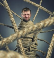 Businessman trapped in rope web
