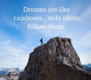 man standing on top of mountain with demotivational quote 'dreams are like rainbows, only idiots follow them
