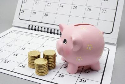 Piggy Bank and Coins on Calendar with Grey Background - speed up your recruitment