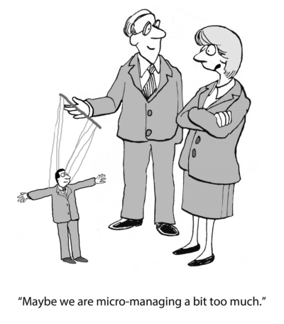 Business cartoon showing boss treating employee as a puppet, 'Maybe we are micro managing a bit too much'.