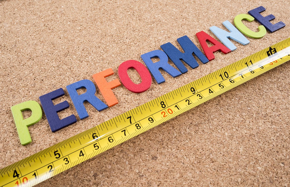 """Word spelling """"Performance"""" and measuring tape on cork board background"""