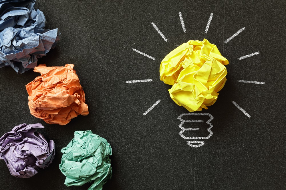 scrunched up pieces of paper with one yellow one in the shape of a lightbulb