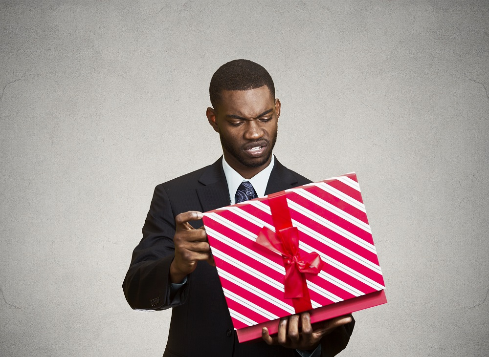 Closeup portrait grumpy, unhappy, upset man holding box, displeased with received gift, disgust on face, isolated grey black background. Negative human emotion, facial expression, feeling attitude